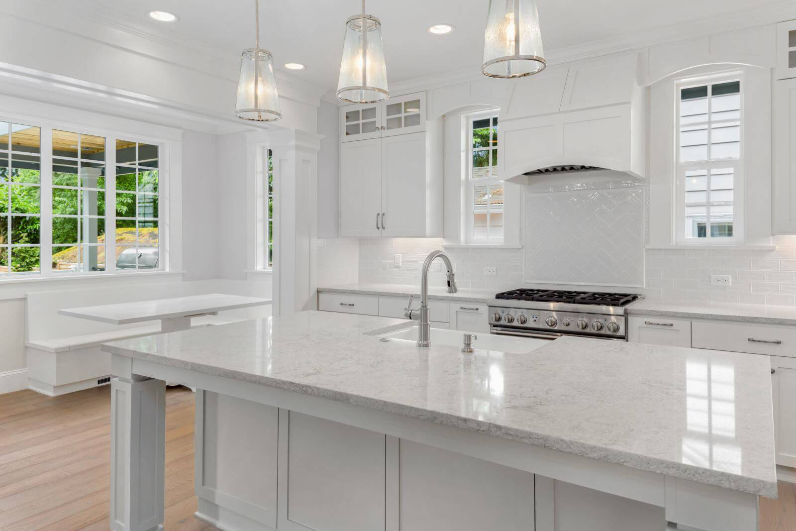 Beautiful White Kitchen in New Luxury Home with Hardwood Floors, Island, and Eating Nook