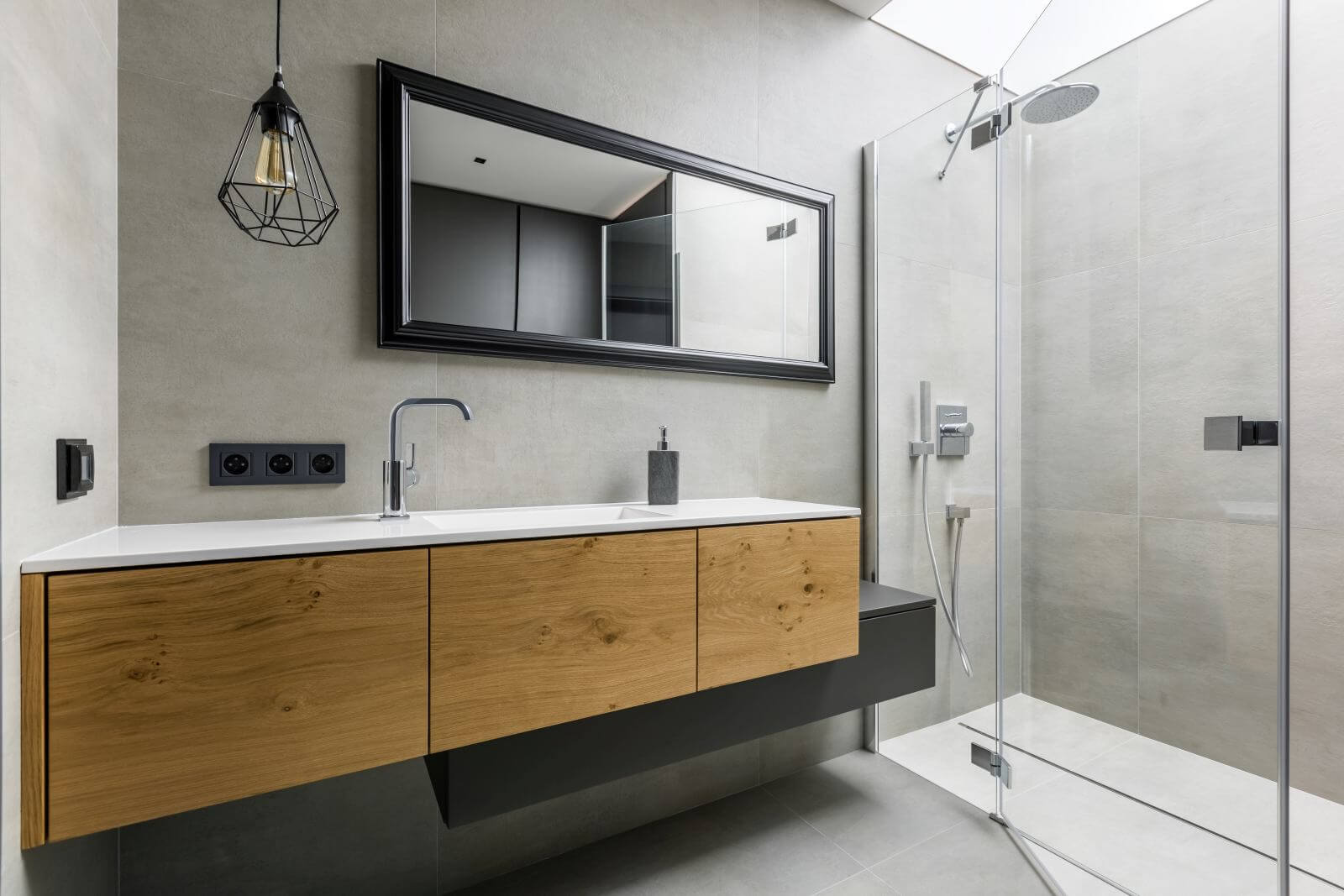 Modern, gray bathroom with walk in shower, mirror and countertop basin