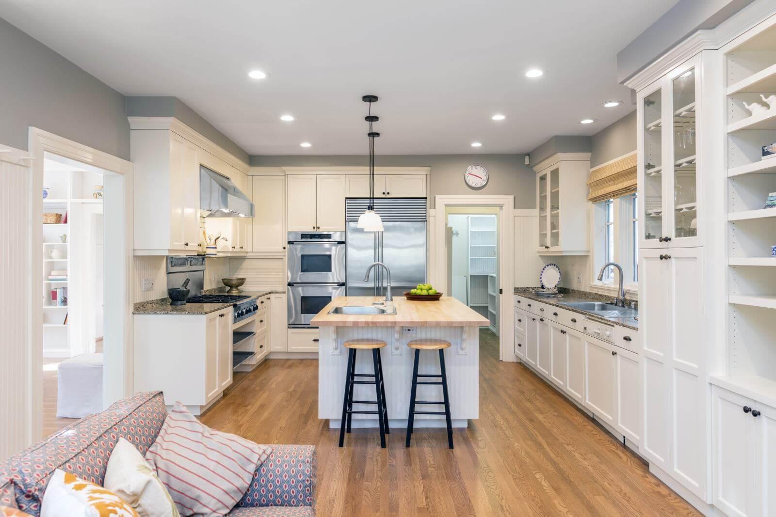 Amazing Luxury Kitchen Interior in white with wooden floor and kitchen island.
