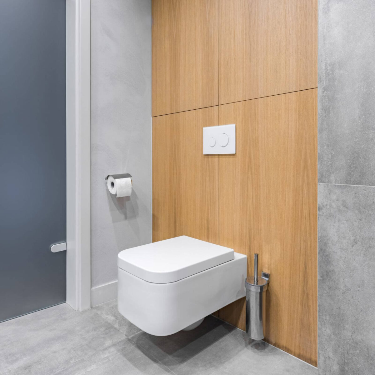 Gray bathroom with white toilet, and modern tiling with wooden details