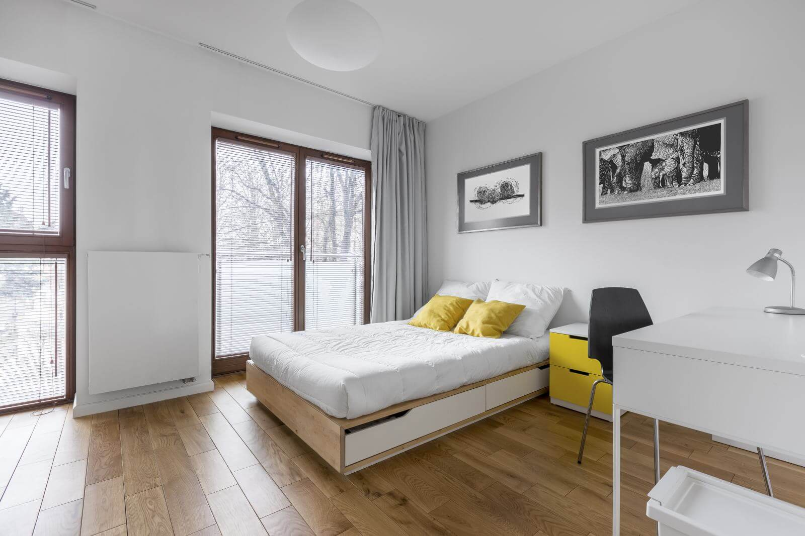 White, multifunctional bedroom with desk, double bed and window