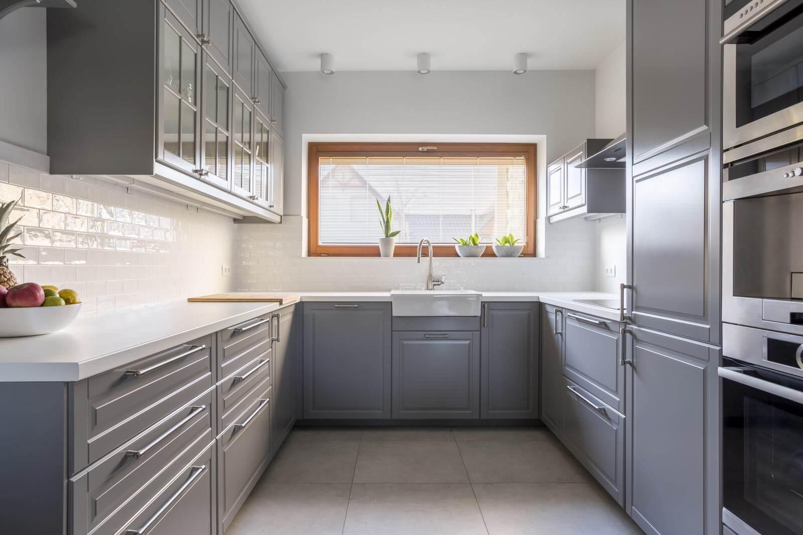 Light, spacious kitchen with window and white brick tiles