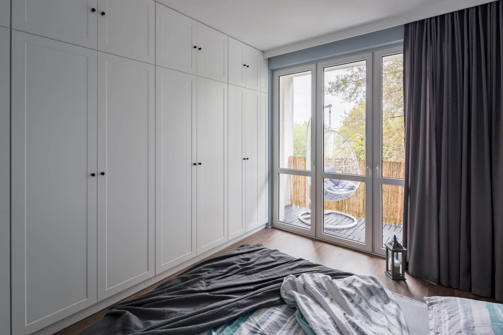 Modern bedroom with big, white wardrobe and window